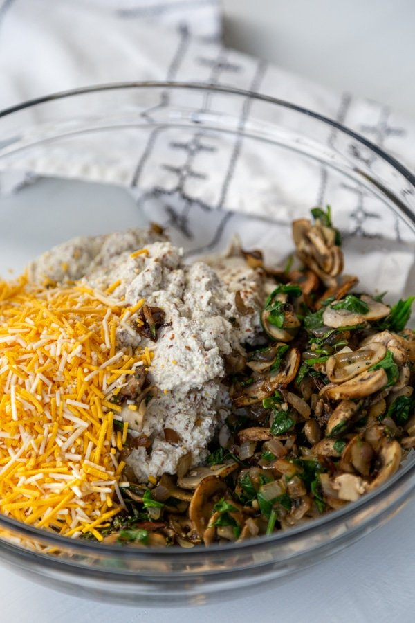 A glass mixing bowl with cheese, mushrooms, onions, spinach, and tofu.