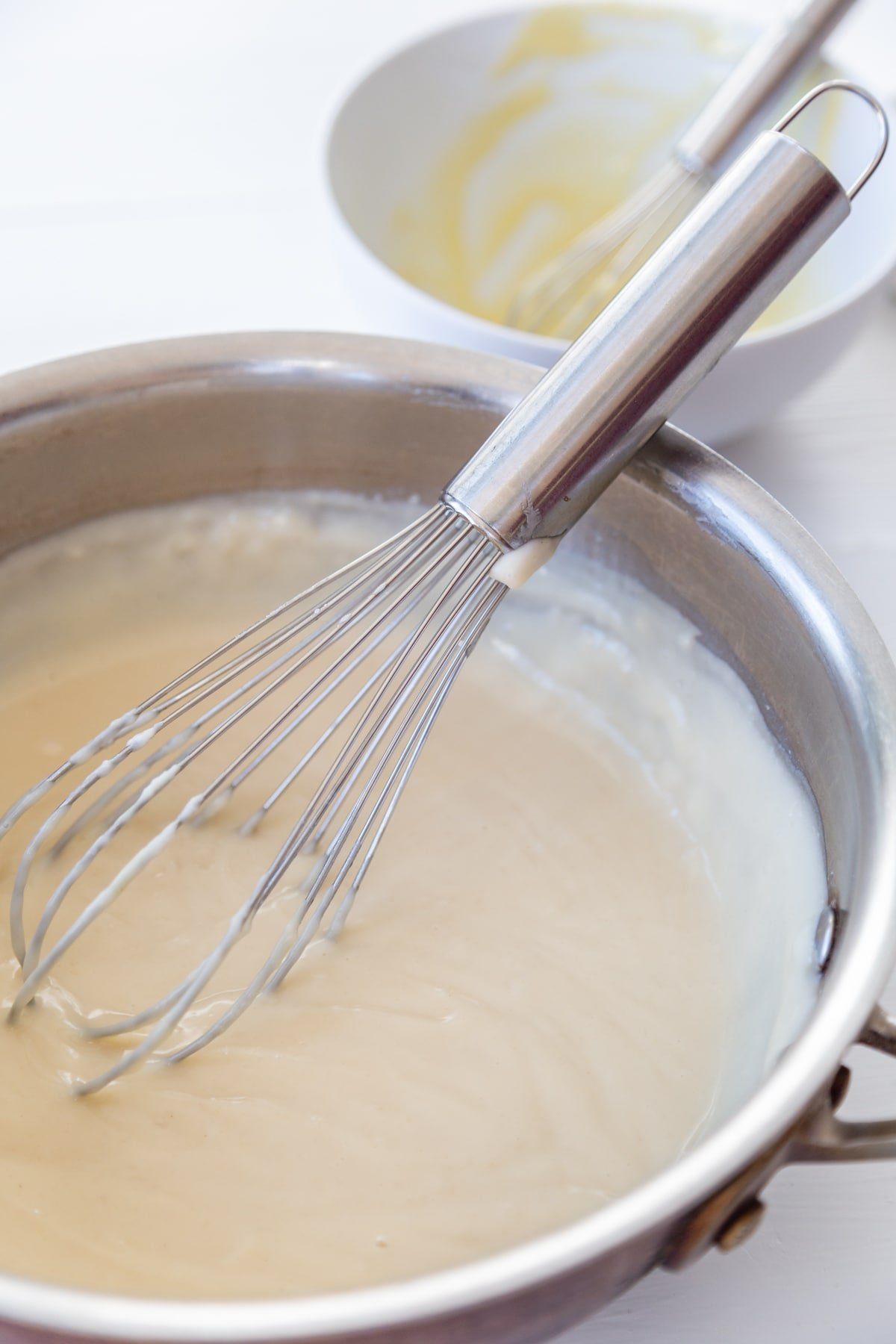 Vanilla pudding being whisked in a copper pot.