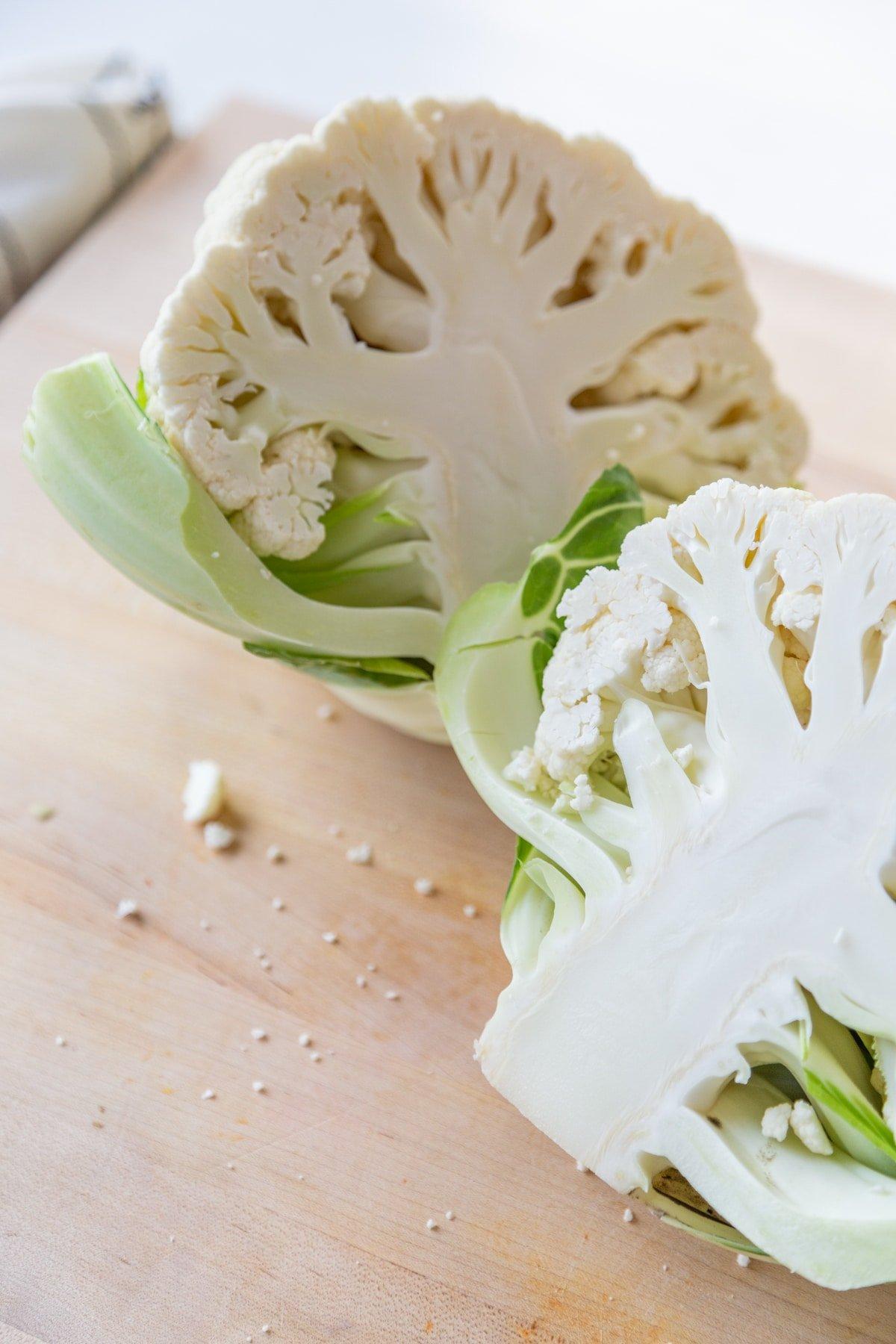 A head of cauliflower cut in half on a wood cutting board.