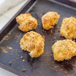 Oven fried breaded cauliflower on a baking sheet with a white and black towel in the background.