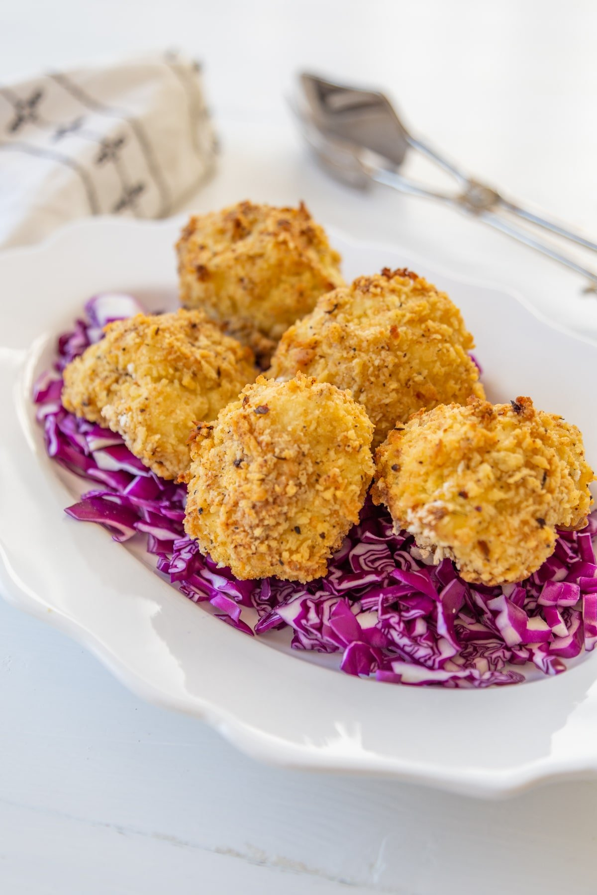 A white scalloped edge plate with a bed or chopped red cabbage with crispy cauliflower on top.