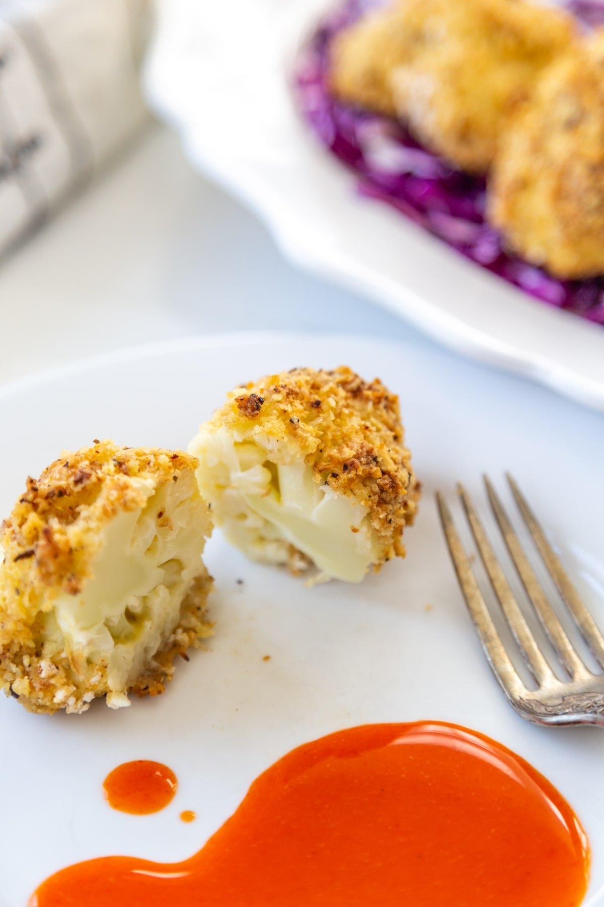 Crispy breaded cauliflower floret cut in half on a white plate with a silver fork and hot sauce on the plate, and a white platter of the cauliflower on a bed of red cabbage in the background.