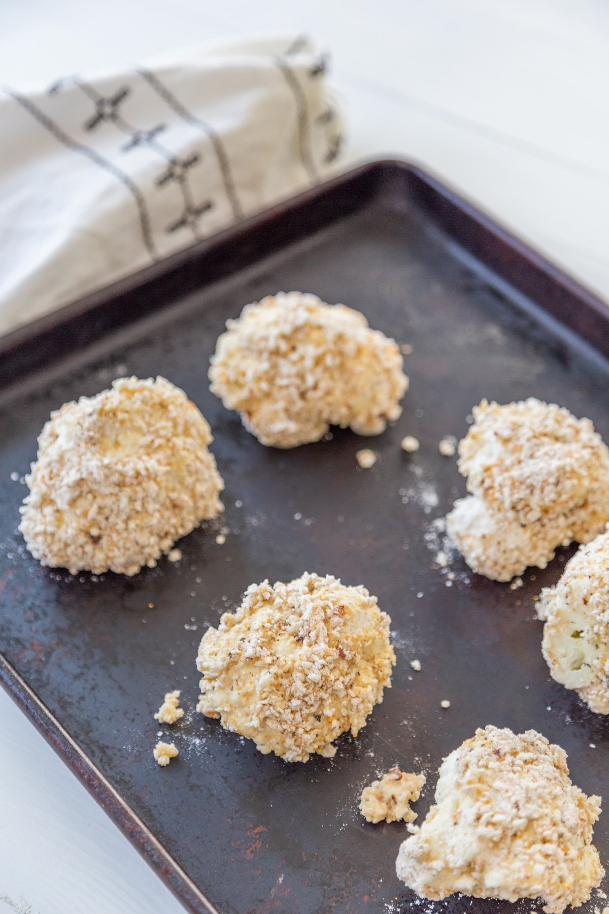 Unbaked cauliflower florets coated in flour and breadcrumbs on a cookie sheet with a white and black towel in the background.