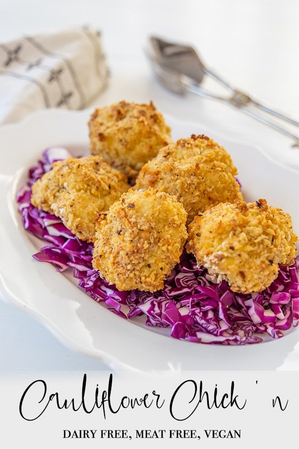 A PInterest pin for vegan oven fried cauliflower with a picture of the cauliflower on a bed of shredded cabbage on a white plate.