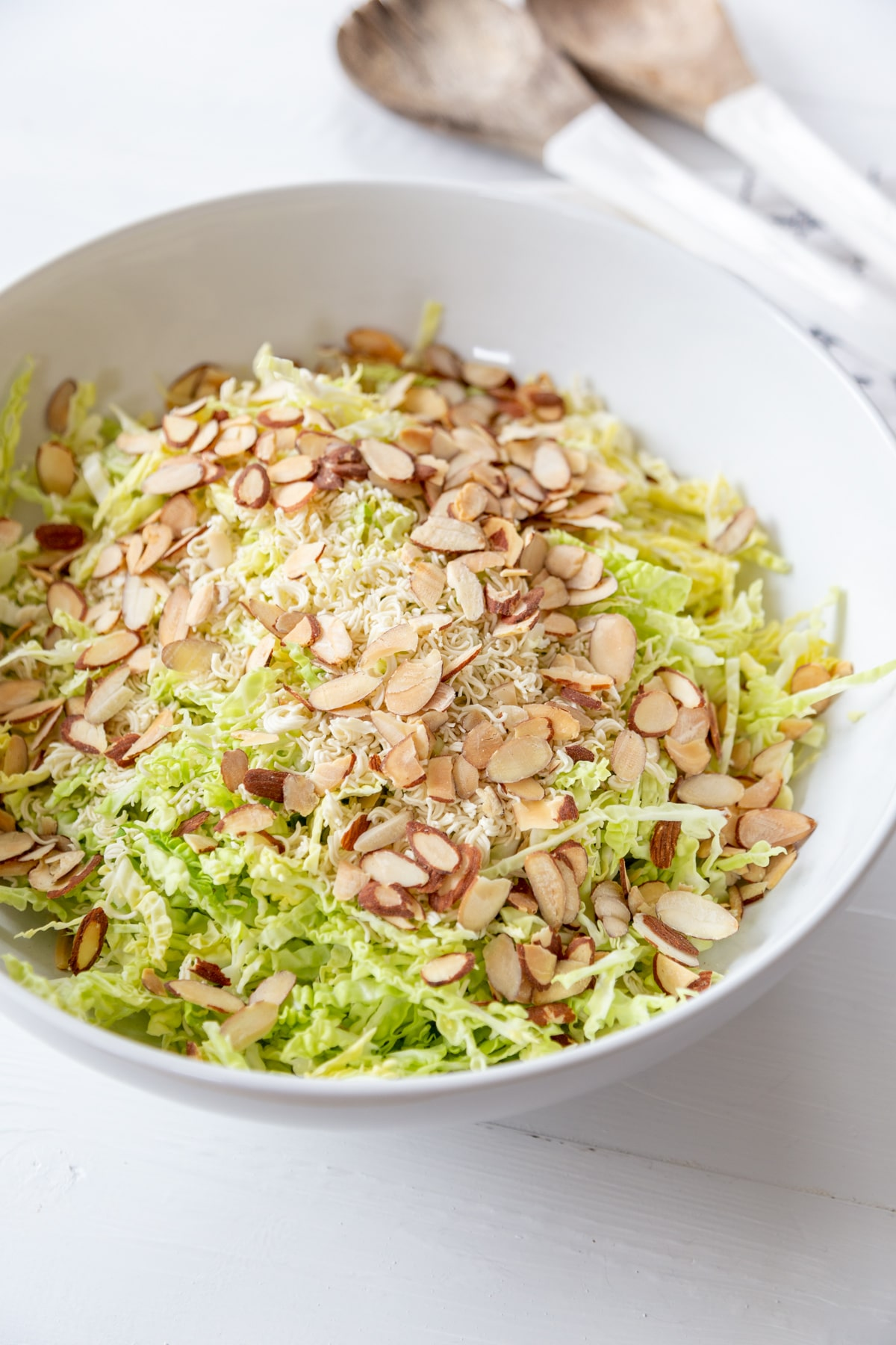 A white bowl with shredded green cabbage and toasted slivered almonds on top of it and a white and wood spoon and fork on the table next to the bowl.
