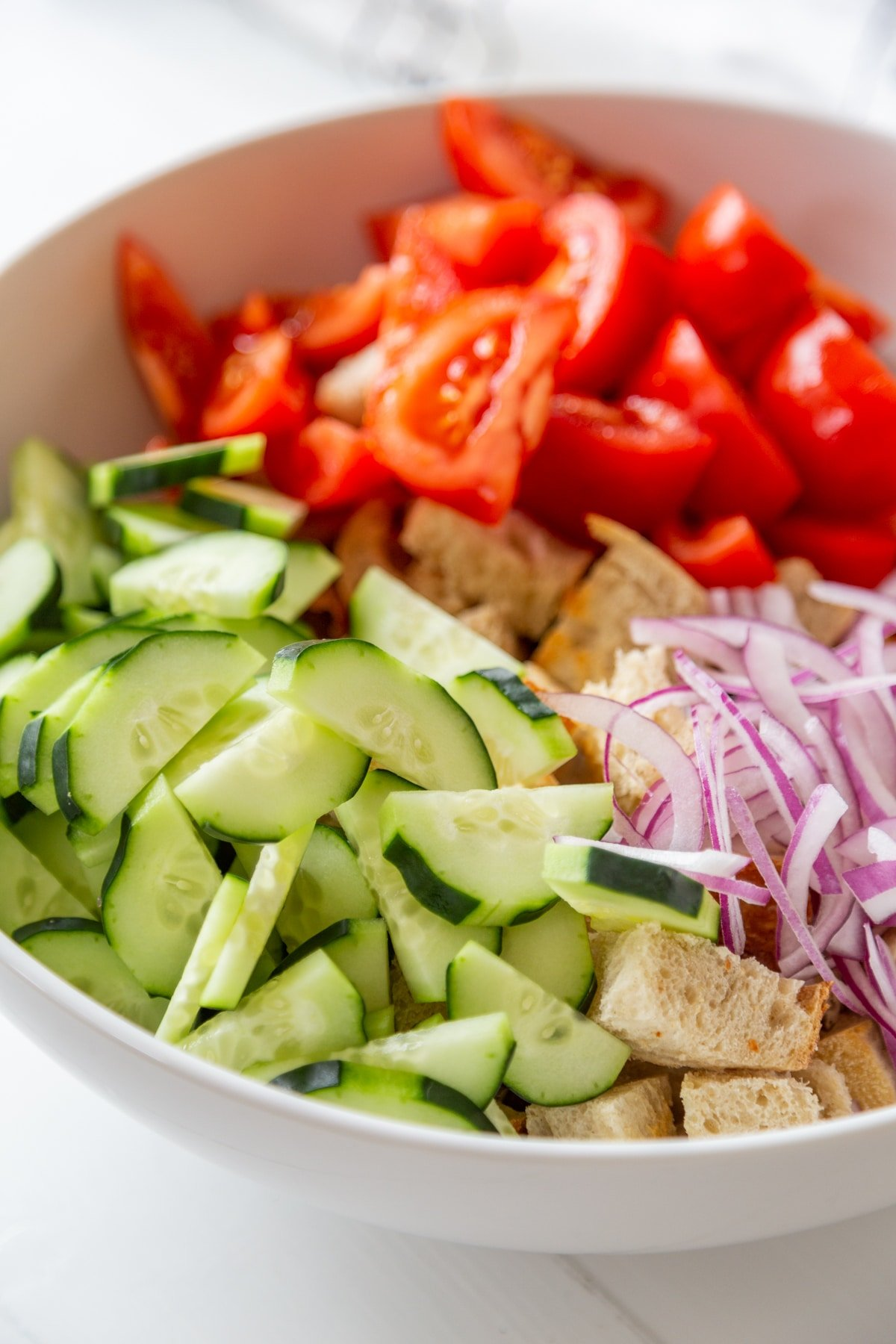 A large white bowl filled with croutons, sliced cucumber, tomatoes, and red onion.