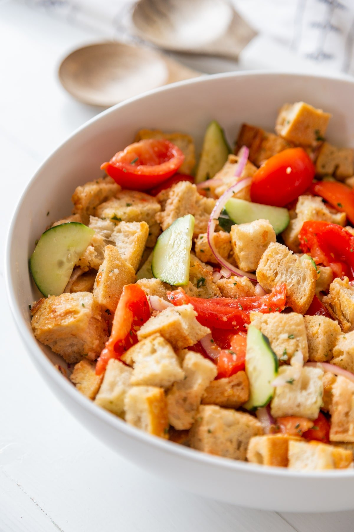 A large white bowl with Panzanella salad and white and wood serving spoons in the background.