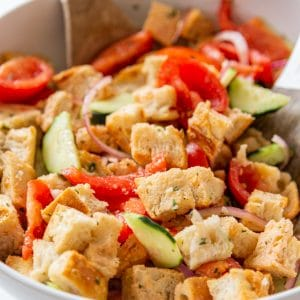 A large white bowl with Panzanella salad and a wood and white serving spoon tossing the salad.