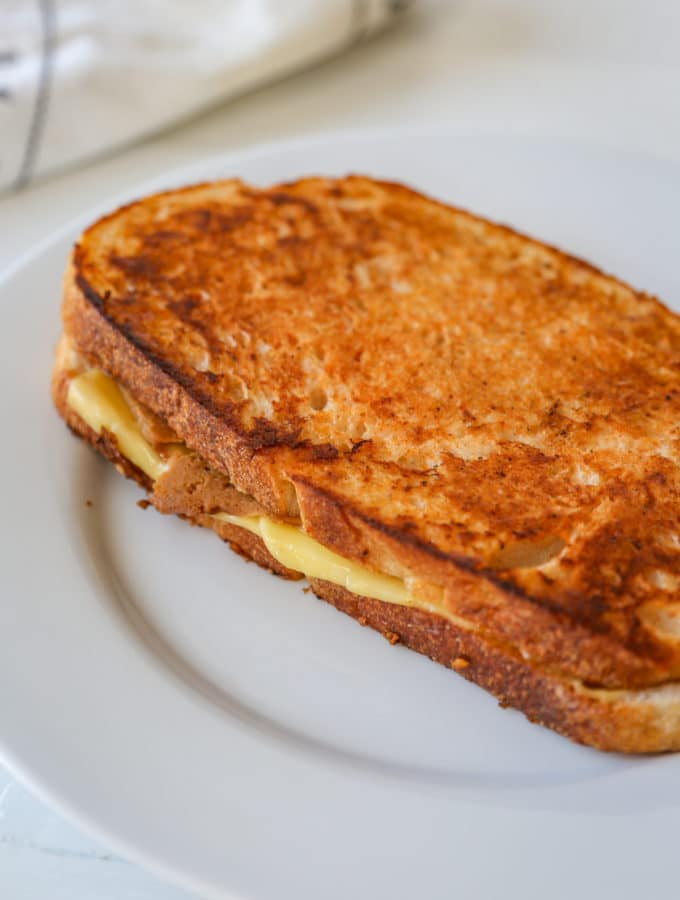 A monte cristo ham and cheese grilled sandwich on a white plate.