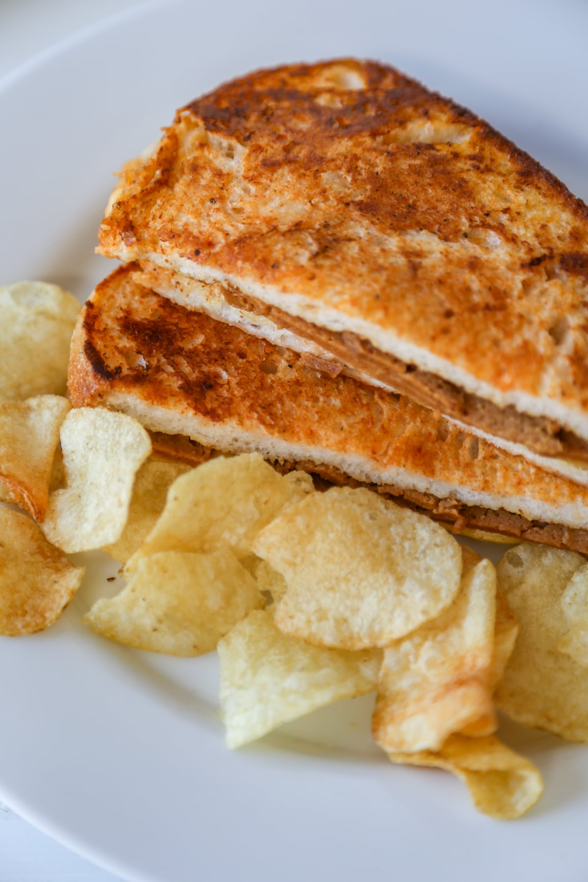 A grilled monte cristo sandwich cut in half in triangles and stacked on a white plate with potato chips.