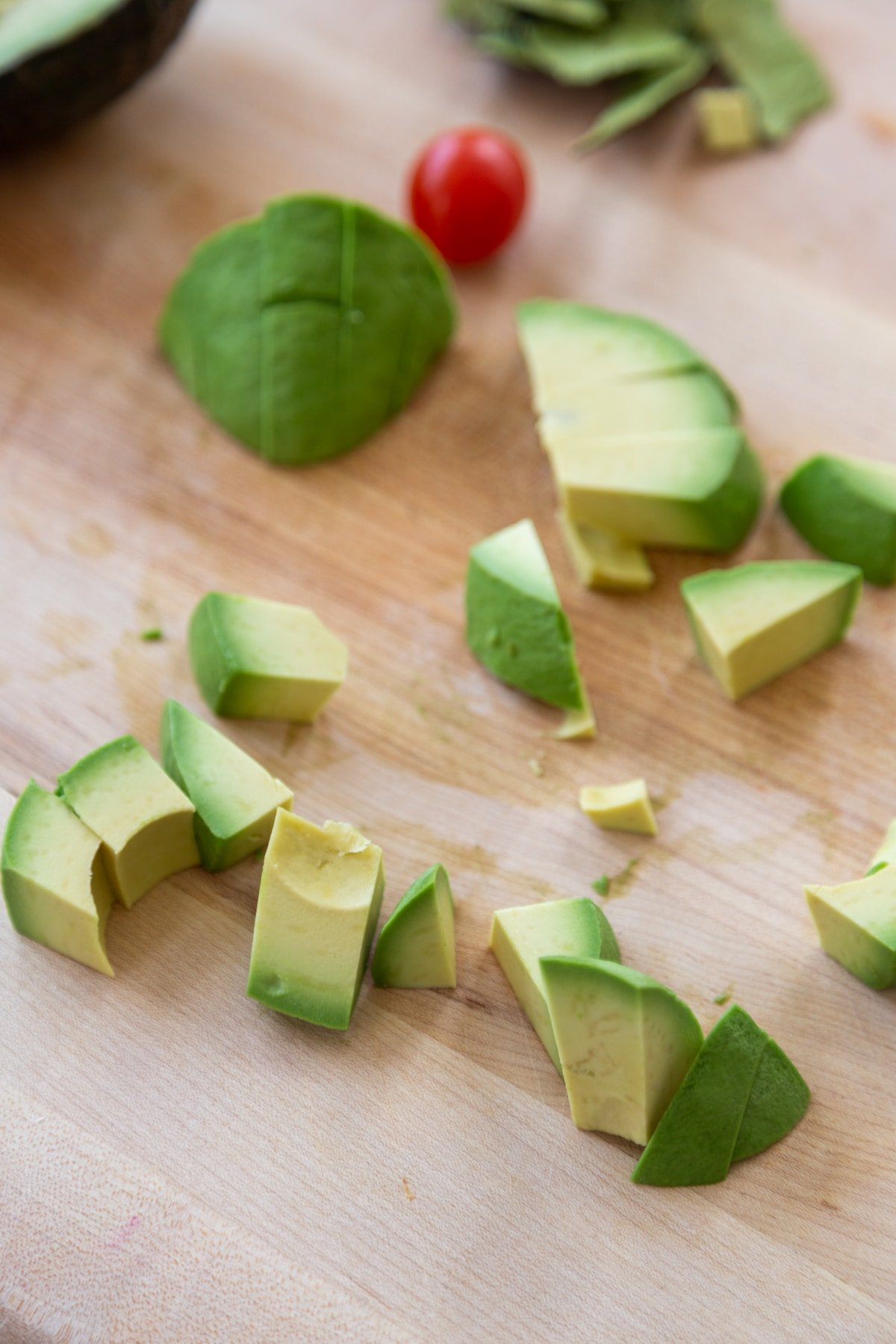 Cubed avocado on a wooden cutting board.