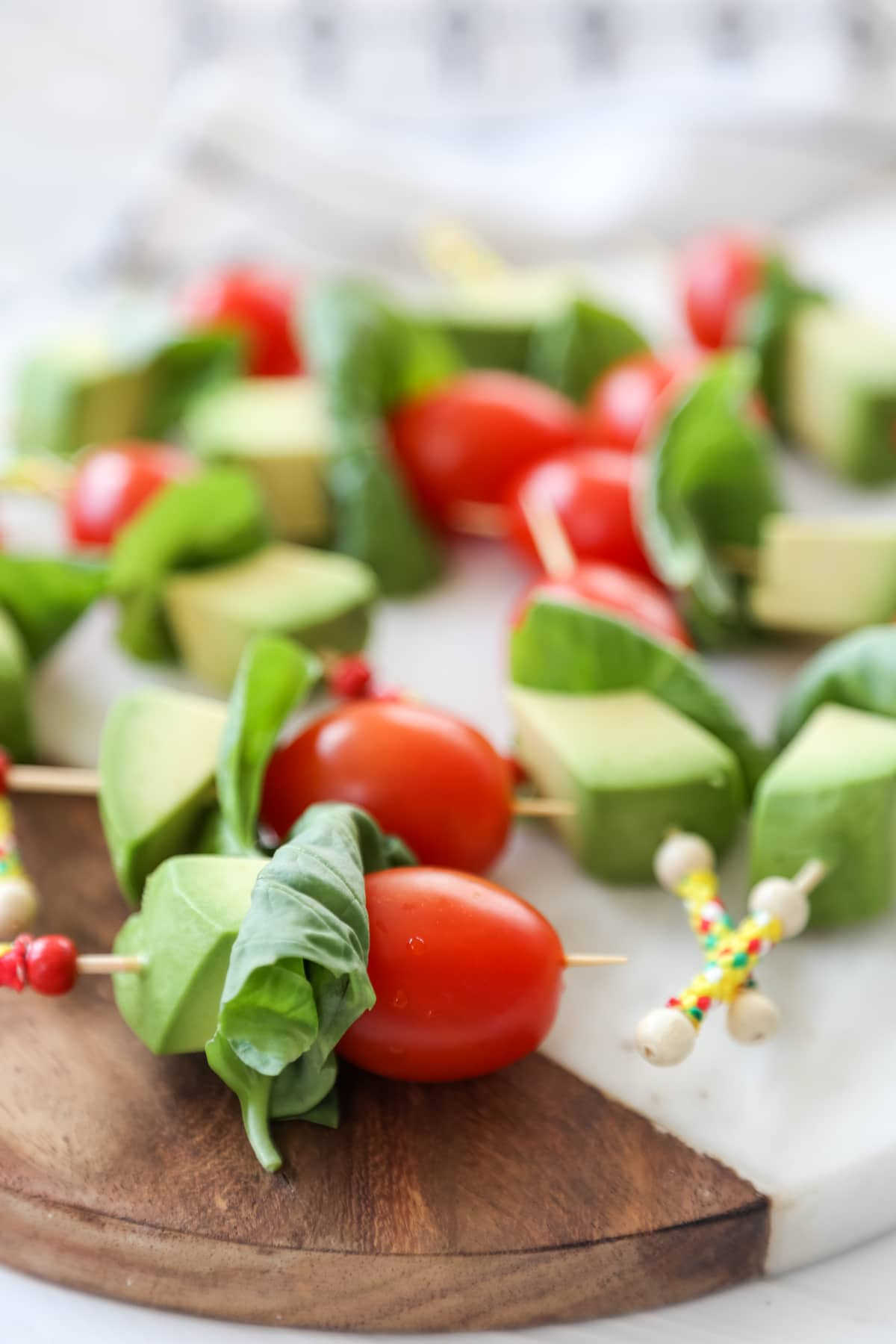 Tomato, basil, and avocado kabobs on a marble and wood board.