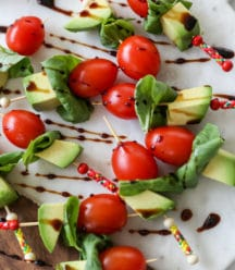 A marble and wood board with tomato, basil, and avocado skewers that are drizzled with balsamic vinegar.