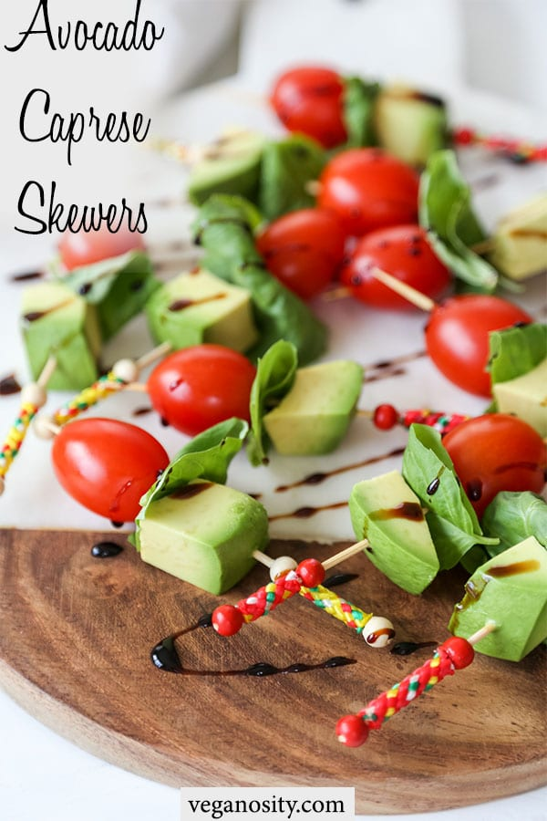 A Pinteres pin for vegan avocado caprese skewers with a picture of the tomato, basil, and avocado skewers drizzled with balsamic vinegar.