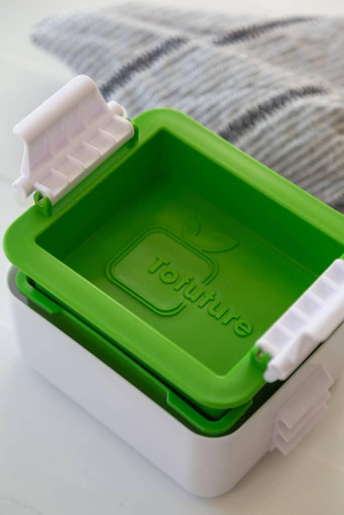 A green and white tofu press with tofu inside.