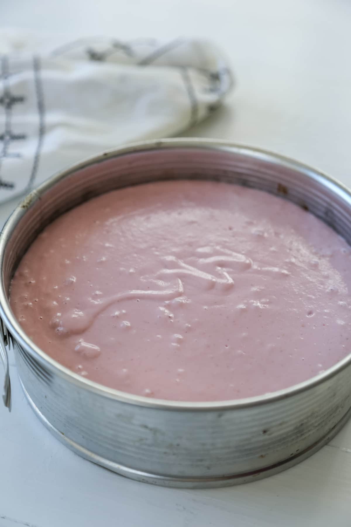 Raspberry cheesecake in a silver springform pan.