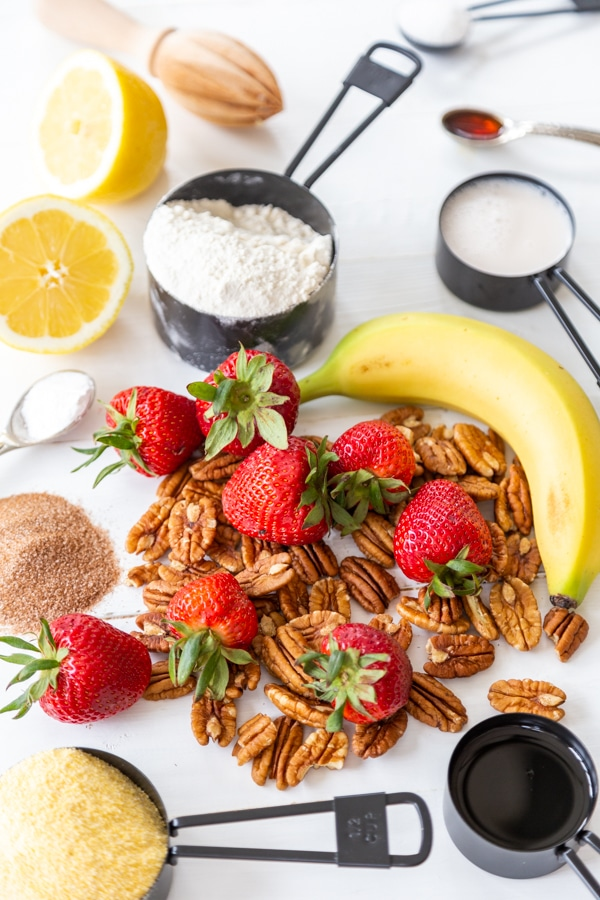 An ingredient photo for strawberry pecan waffles with measuring cups of flour, cornmeal, sugar, and strawberries, pecans, a banana, and lemon on a white table.
