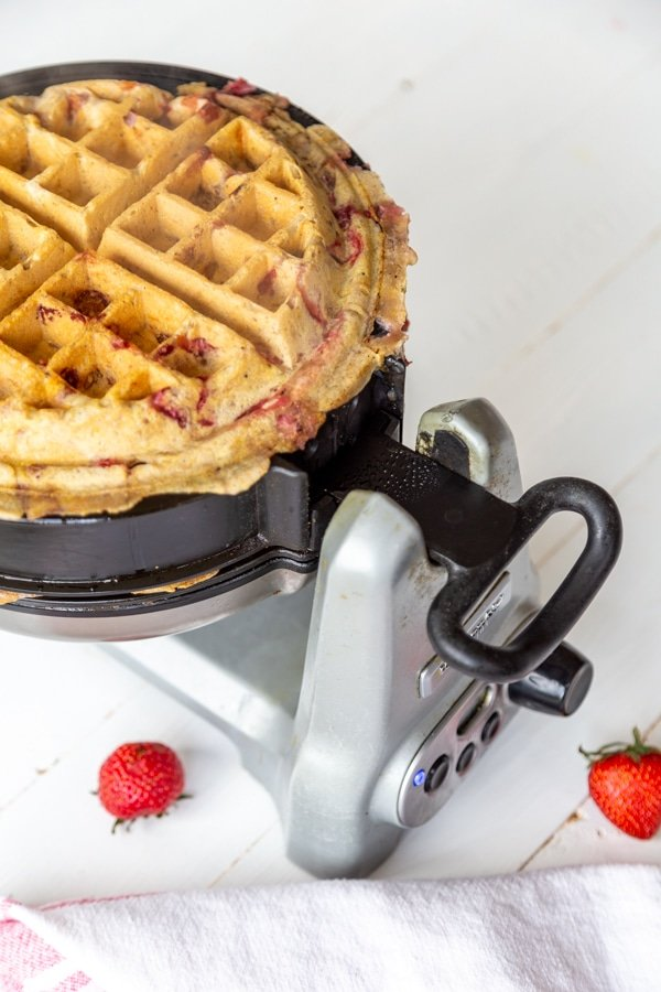 A strawberry pecan waffle in a waffle iron.