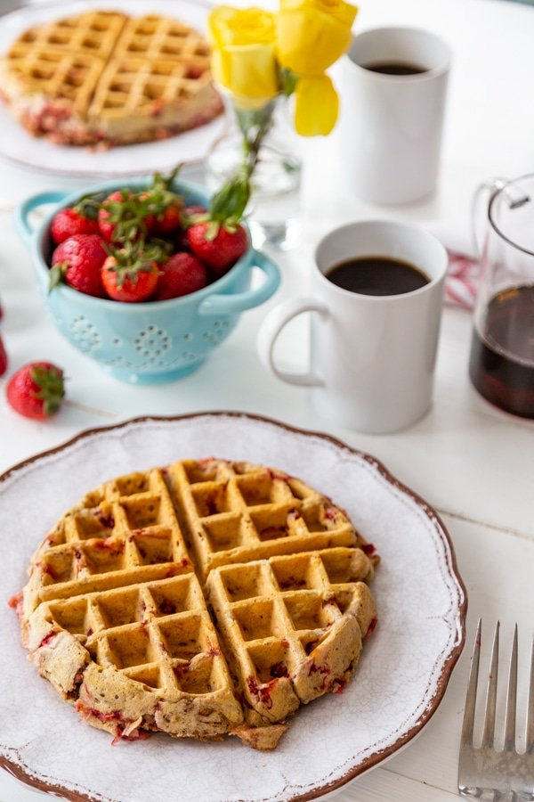 Two white plates with strawberry pecan Belgian waffles and a blue bowl of strawberries and 2 cups of coffee.