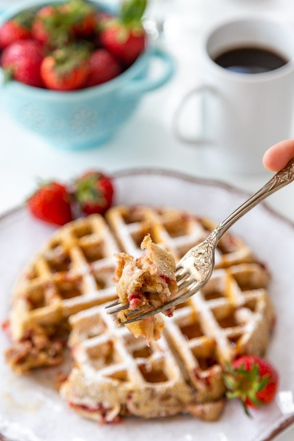 A fork full of a strawberry pecan waffle being held over a white plate with the waffle and a bowl of strawberries and cup of coffee.