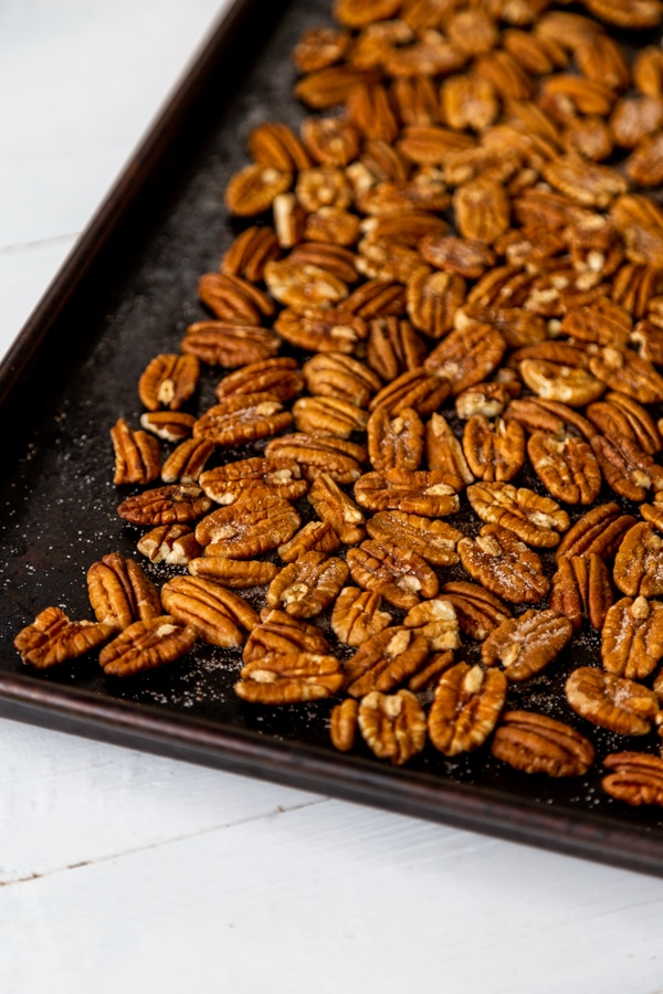 A rimmed baking sheet filled with toasted pecans.