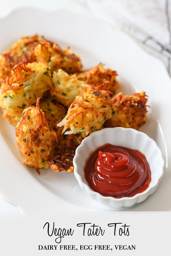 A PInterest pin for cheesy vegan tater tots with a picture of a white platter with tots and a white dish of ketchup.