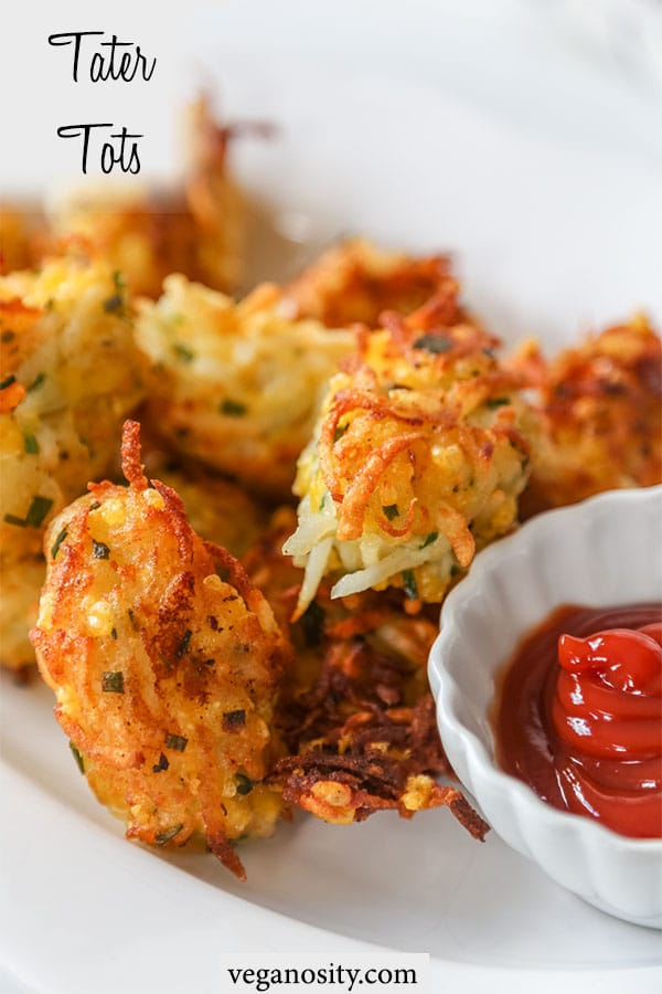 A Pinterest pin for cheesy vegan tater tots with a picture of a white platter of tots and a white scalloped dish with ketchup.
