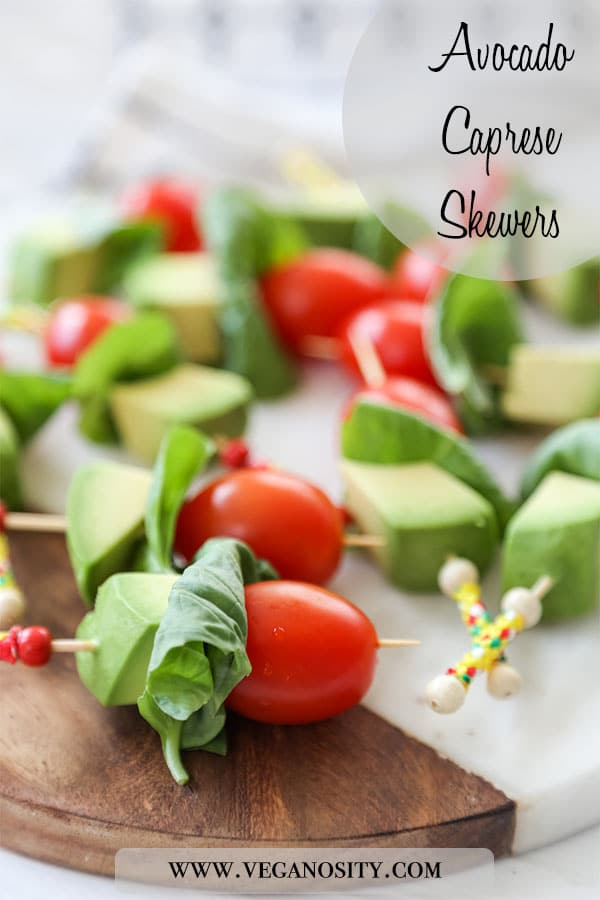 A Pinterest pin with a close up picture of avocado caprese skewers on a wood and marble board.