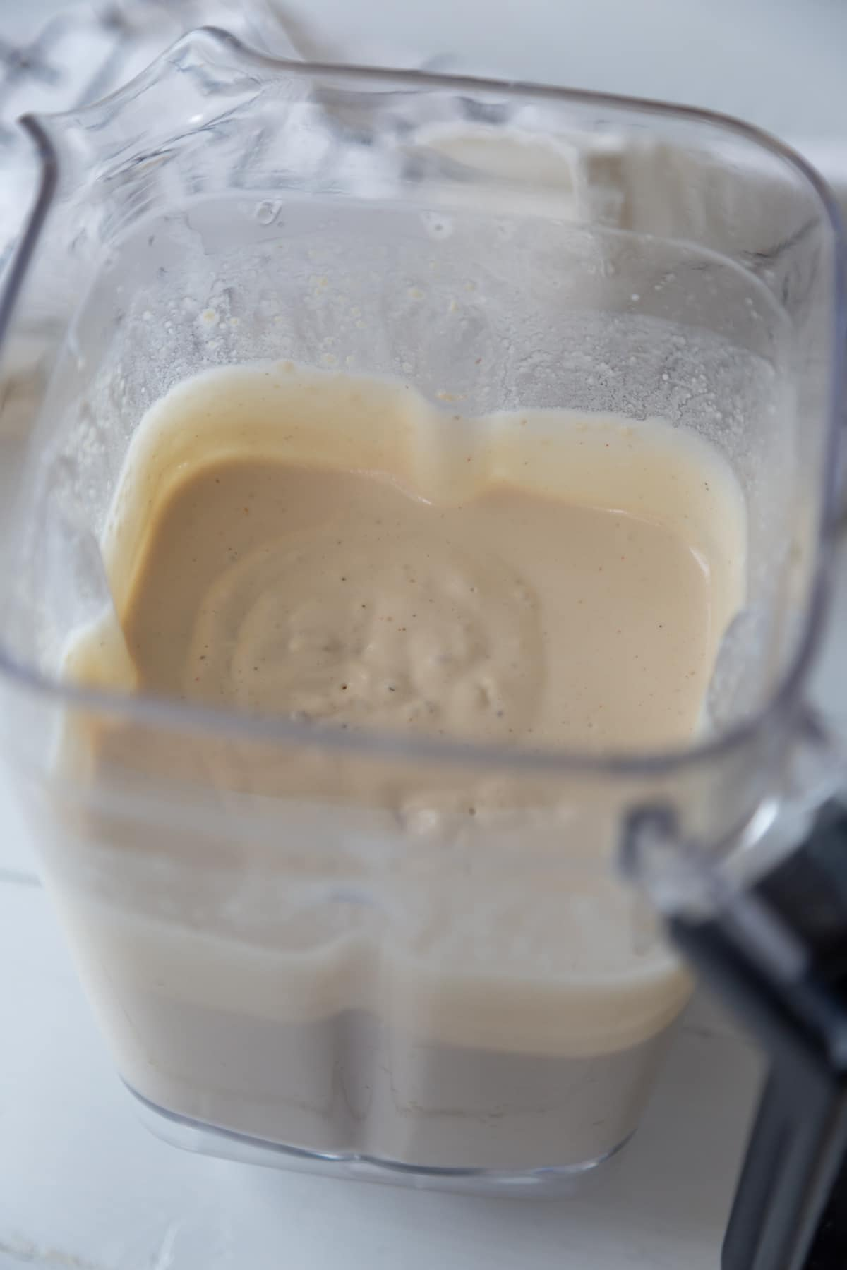 A blender with white cream sauce.