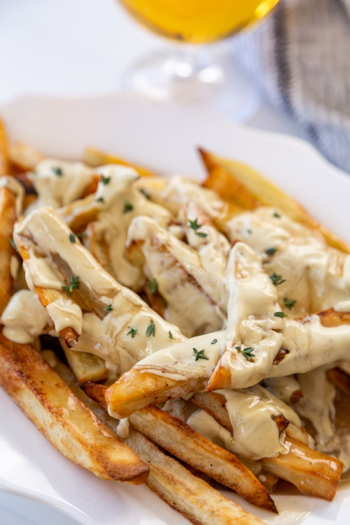 A white oval platter with fries that are covered in cheese sauce and gravy, and sprinkled with minced chives.