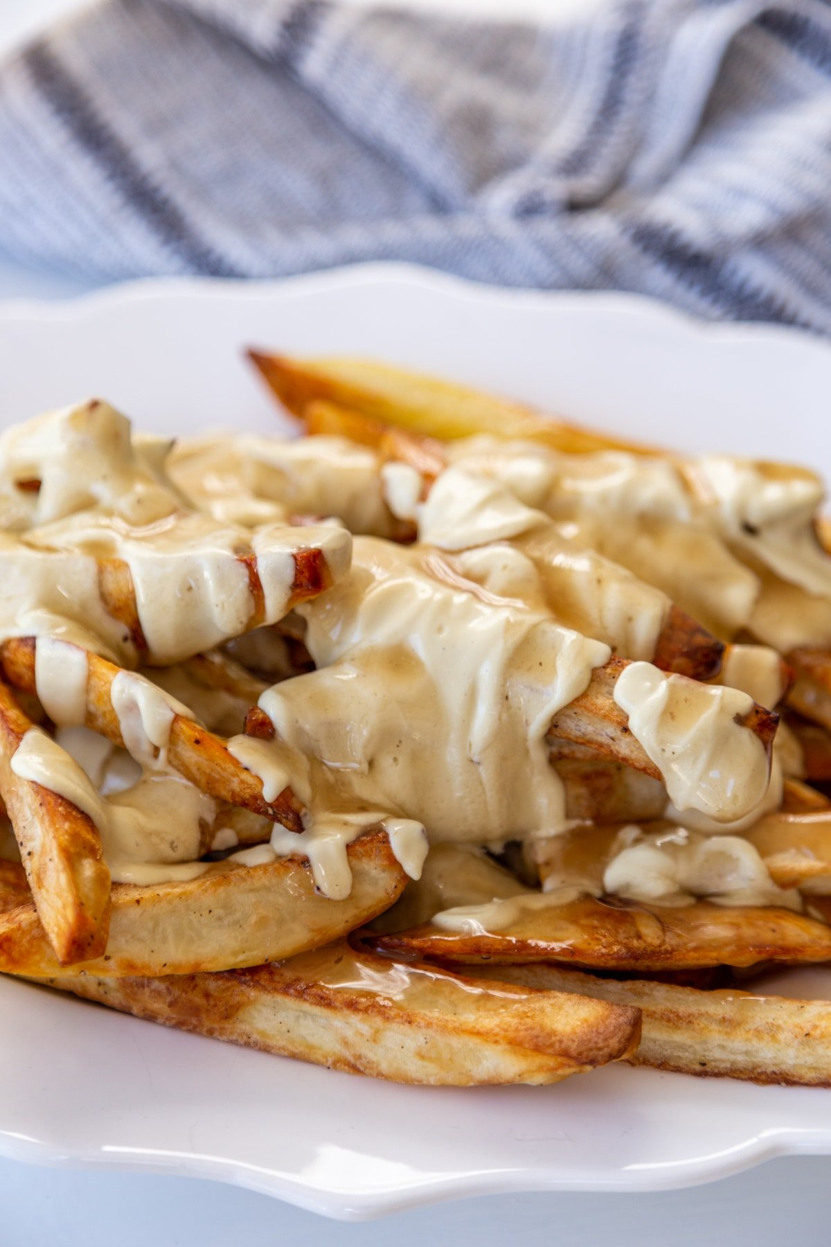 An oval white scalloped platter filled with poutine and a white and black striped towel in the background.