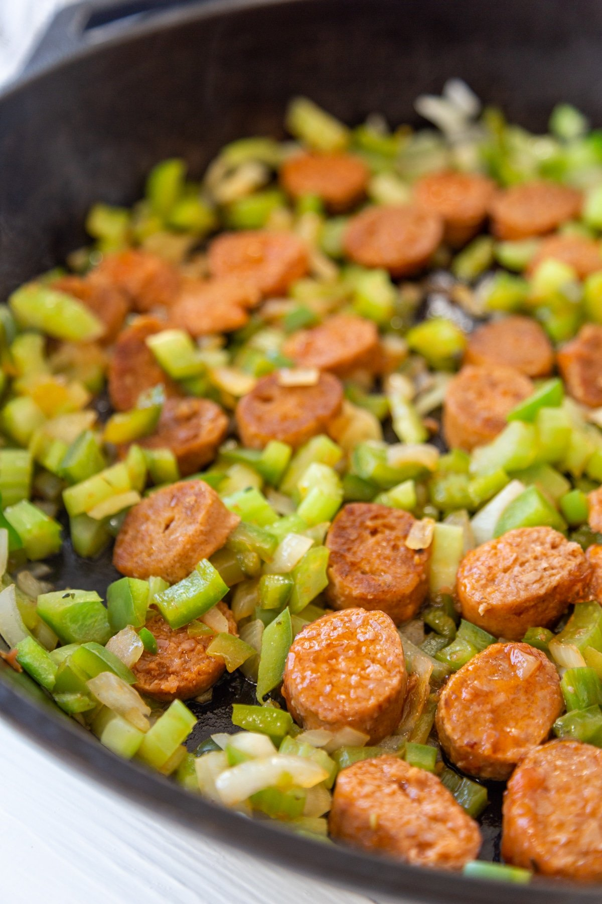 An iron skillet with onions, green bell pepper, celery, and sausage.