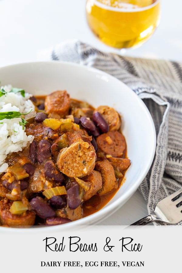 A Pinterest pin for vegan red beans and rice with the beans and rice in a white bowl with a glass of beer in the background.