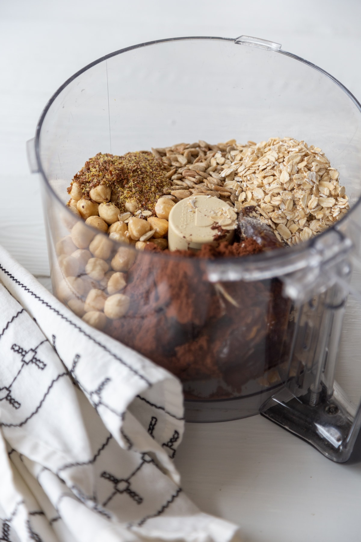 A food processor filled with rolled oats, dates, cocoa powder, and hazelnuts.