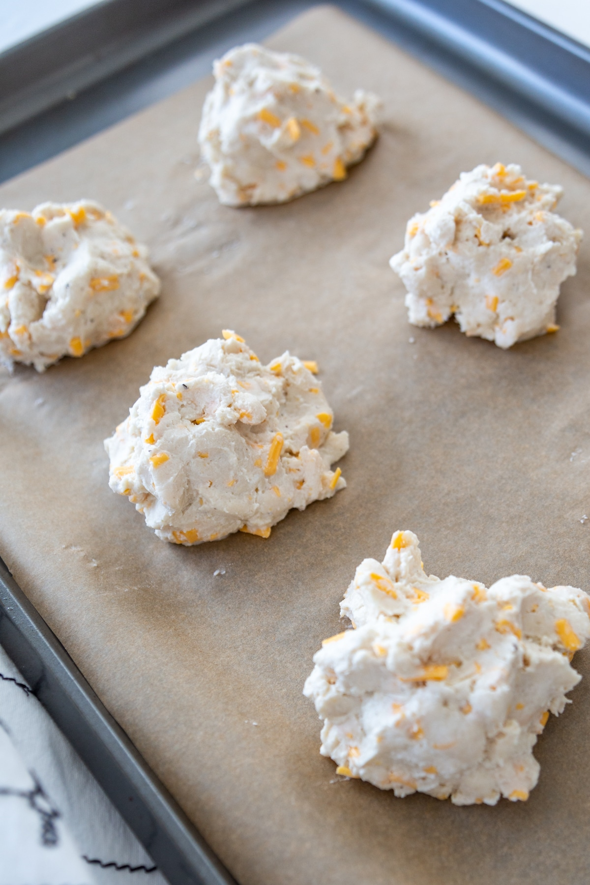 Unbaked cheddar drop biscuits on a parchment lined baking sheet.