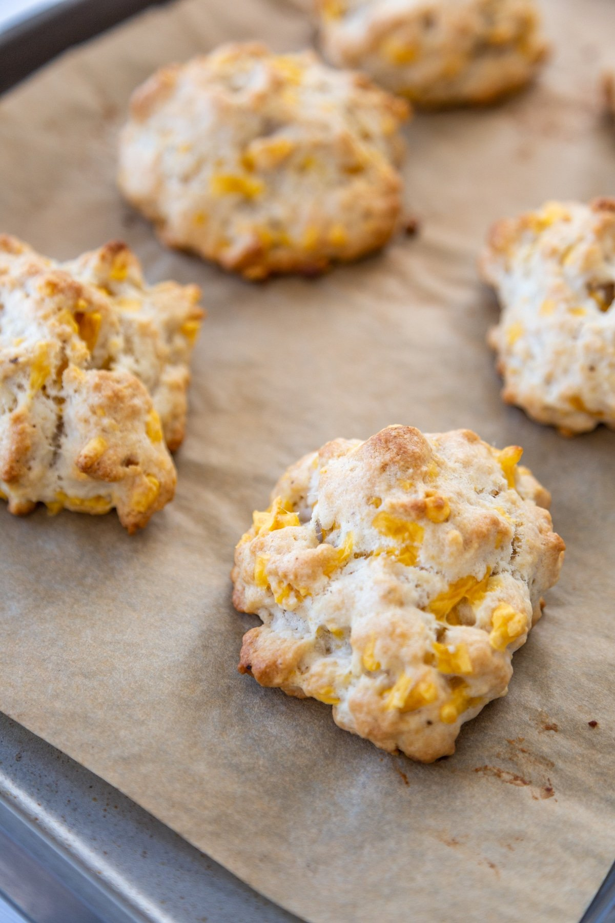 Cheddar drop biscuits on a parchment paper lined baking sheet.
