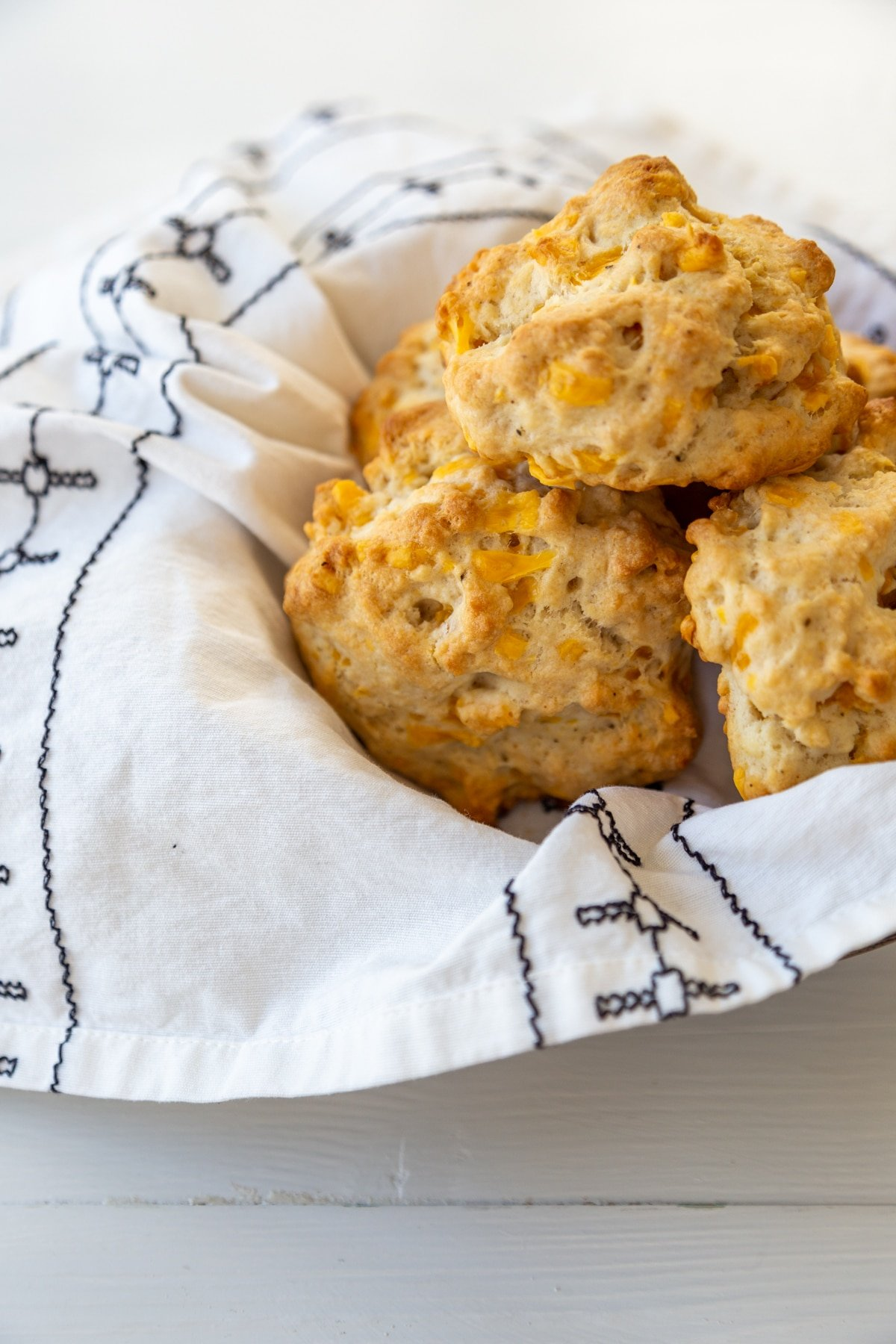 Cheddar drop biscuits in a bowl lined with a white and black patterned napkin.
