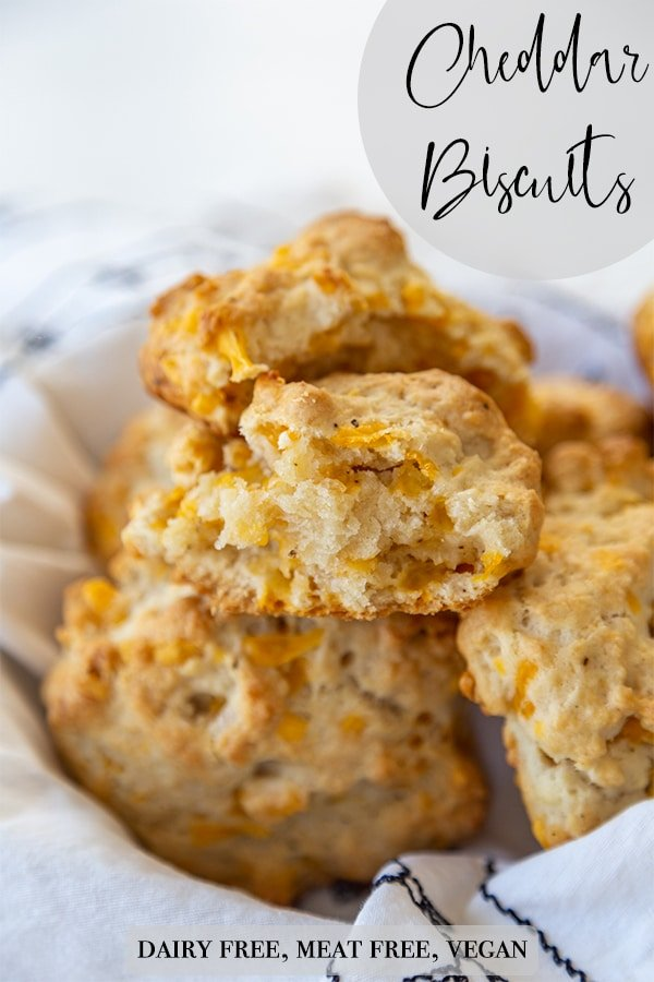 A Pinterest pin for vegan cheddar drop biscuits in a basket with the top biscuit torn in half to show the center.