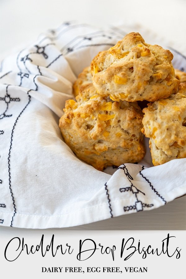 A Pinterest pin for vegan cheddar drop biscuits with a pile of the biscuits in a basket with a white and black napkin.