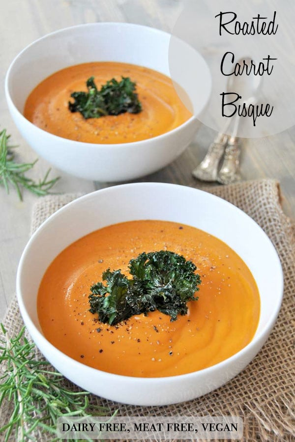 A Pinterest pin for vegan roasted carrot soup with a picture of two white bowls of soup with kale chips in the middle of the soup.