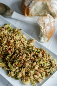 A rectangular white platter with a couscous and Brussels sprouts salad and a loaf of bread with a piece torn off of it next to the platter.