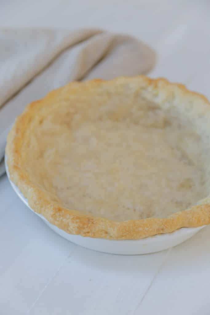 A baked vegan pie crust in a white pie plate.