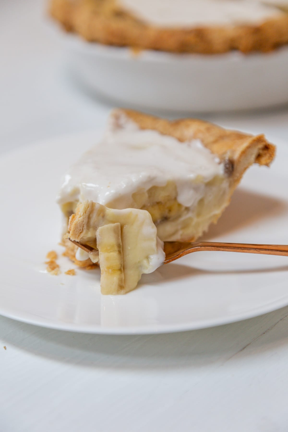 A slice of banana cream pie with a copper fork digging into the pie.