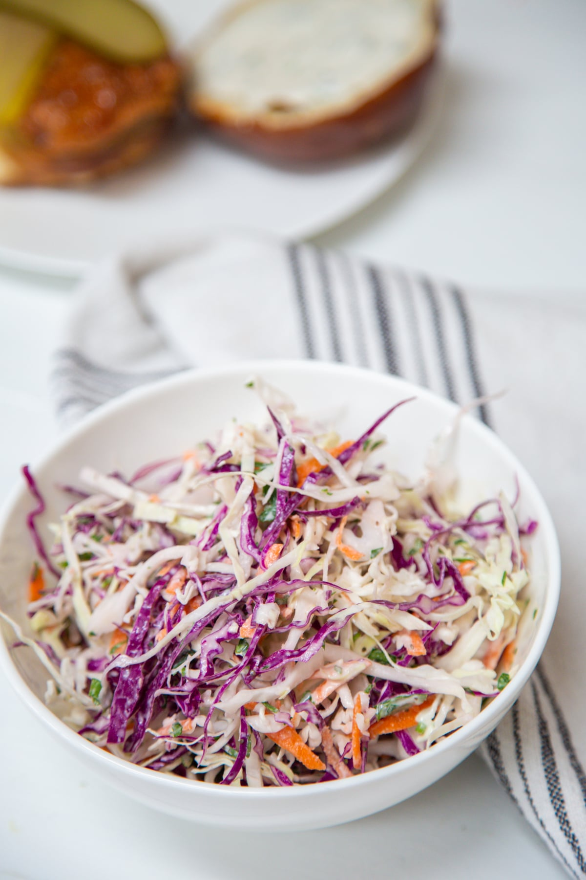 Red and green cabbage creamy coleslaw in a white bowl next to a white and black striped towel with a bun in the background.