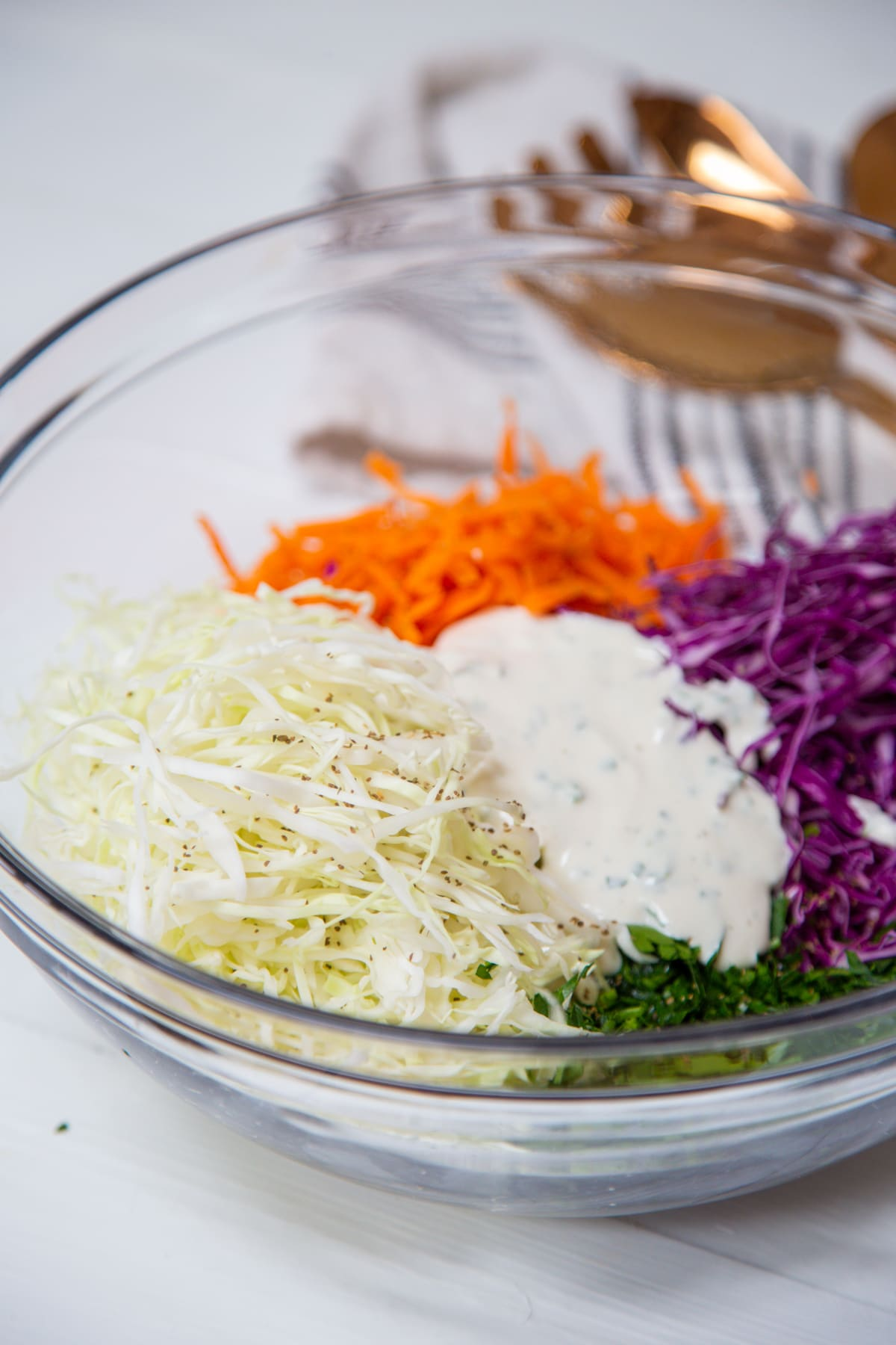 A clear glass bowl with shredded green and purple cabbage, grated carrots, chopped parsley, and a white creamy dressing.