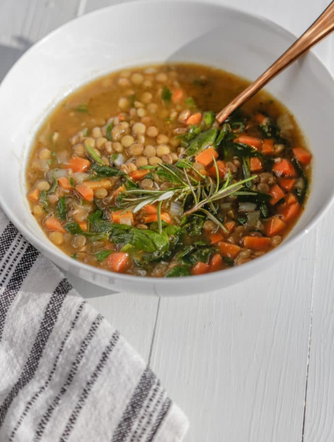 A white bowl with vegetable lentil soup with a copper spoon in the bowl and a white and black towel next to the bowl.