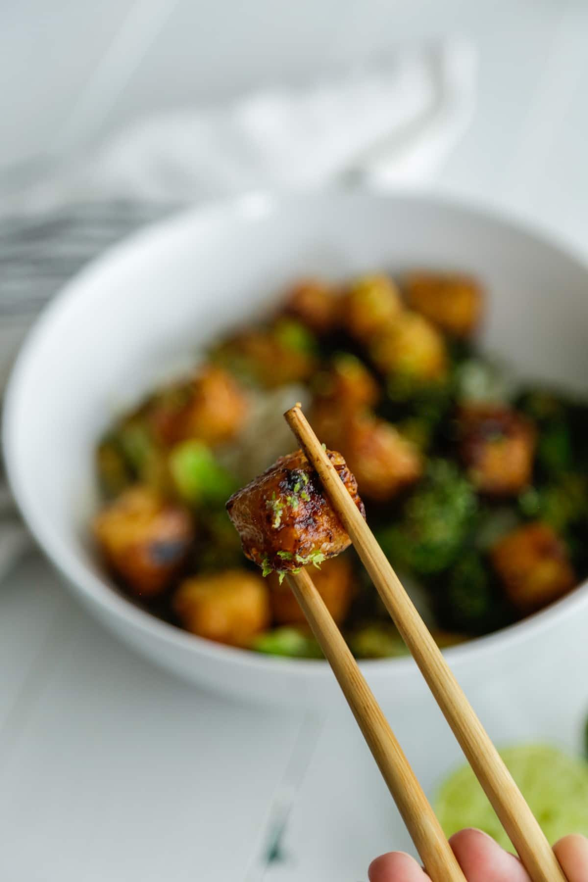 A pair of chopsticks holding a piece of tofu over a white bowl filled with the tofu, broccoli, and rice.