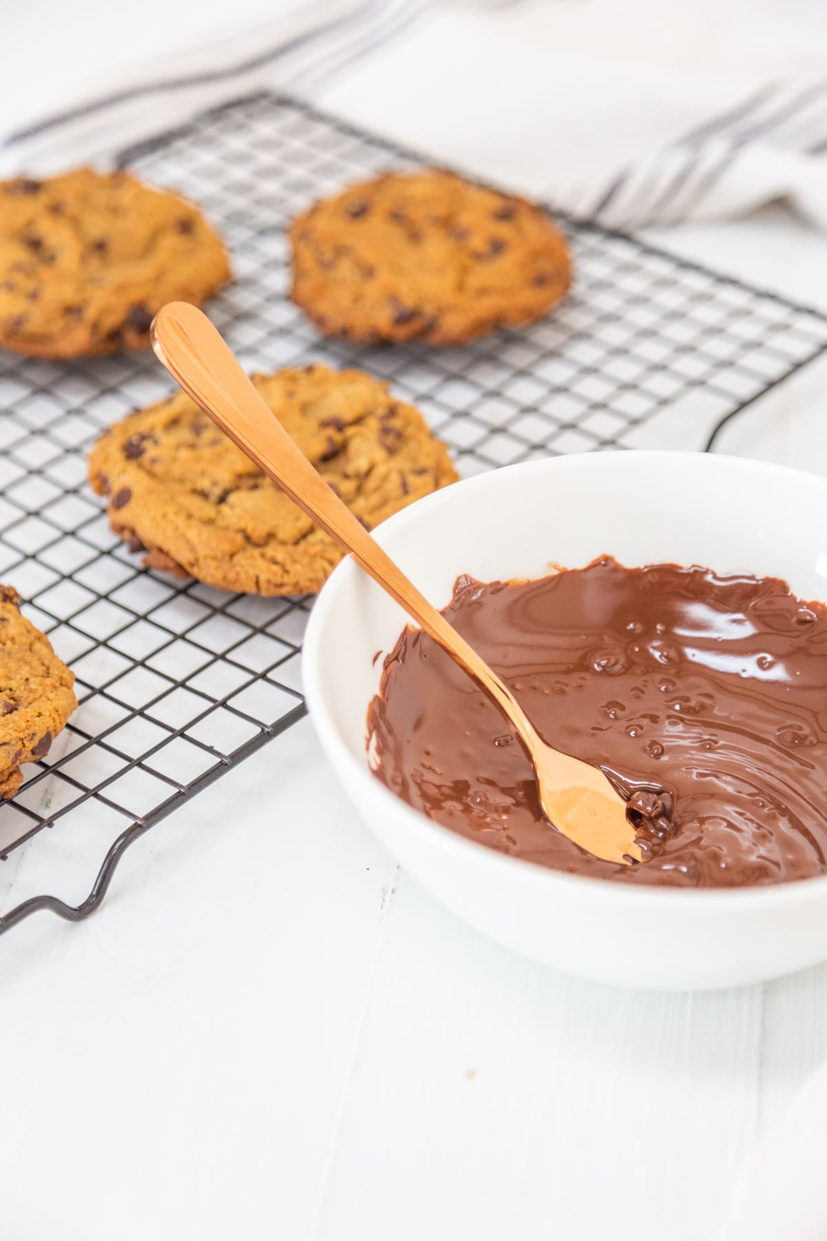 A white bowl of melted chocolate with a copper spoon next to a cooling rack with chocolate chip cookies.