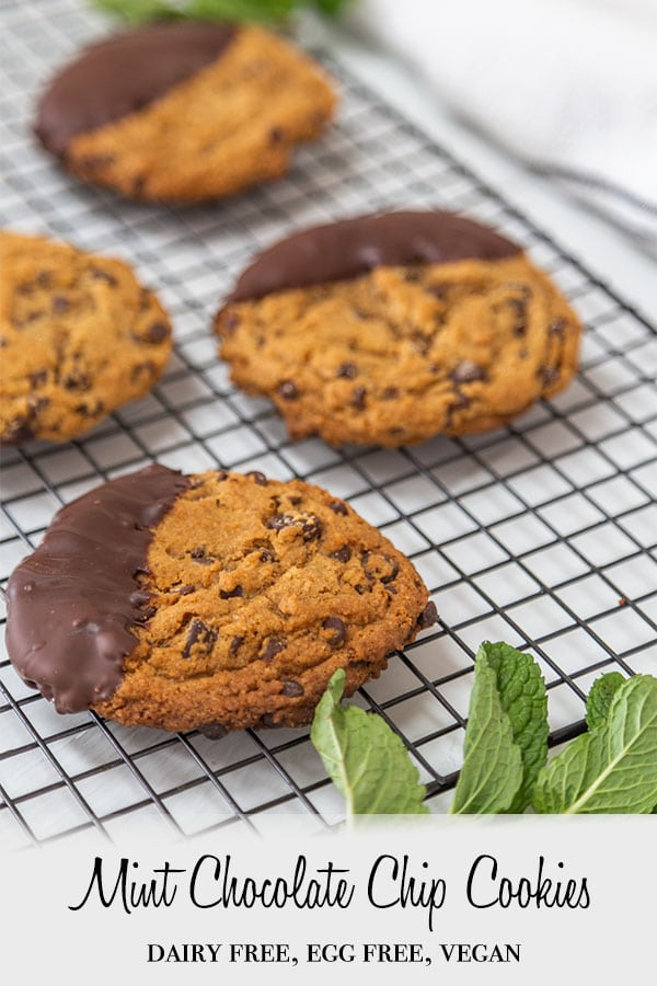 A Pinterest pin for vegan mint chocolate chip cookies with chocolate dipped cookies on a cooling rack with mint leaves.