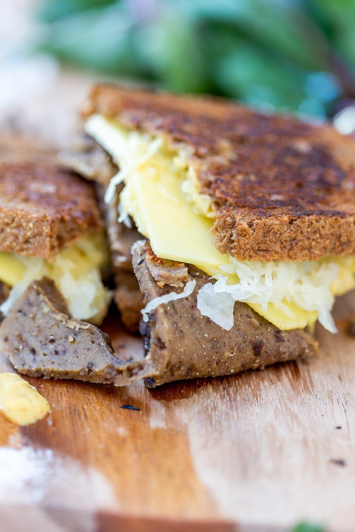 A Reuben sandwich on a wooden board.